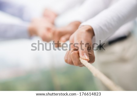 Concept image of business team using a rope as an element of the teamwork on the foreground  Royalty-Free Stock Photo #176614823