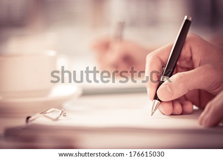 Close shot of a human hand writing something on the paper on the foreground  Royalty-Free Stock Photo #176615030