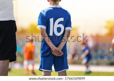 Soccer Boy in Blue Uniform on The Field. School Kid Standing with Coach. Youth Sports Competition in the Blurred Background