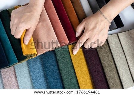 The woman points to the colored fabric that she likes, she chooses the fabric in the catalog with fabric samples for her new sofa. Flat lay Royalty-Free Stock Photo #1766194481