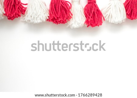 brushes from yarn of red and white color on a white background. Space for copy space. DIY yarn brushes. Garland. Garland of yarn. Pampushki from yarn. Children's creativity #1766289428