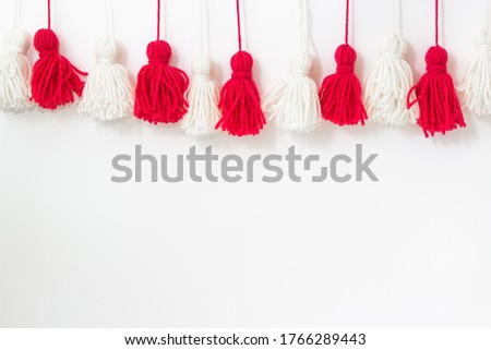 brushes from yarn of red and white color on a white background. Space for copy space. DIY yarn brushes. Garland. Garland of yarn. Pampushki from yarn. Children's creativity #1766289443