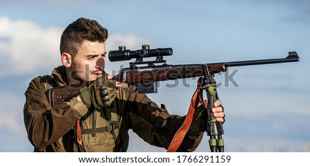 Hunter with hunting gun and hunting form to hunt. Hunter is aiming. Hunter man. Shooter sighting in the target. Hunting period. Male with a gun. Close up. The man is on the hunt. Hunt hunting rifle. #1766291159