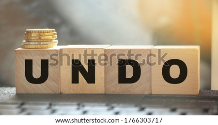 Undo word on wooden cubes with letters, and stack of coins. Technical issue computer program concept. Lifestyle and state of mind concept. #1766303717