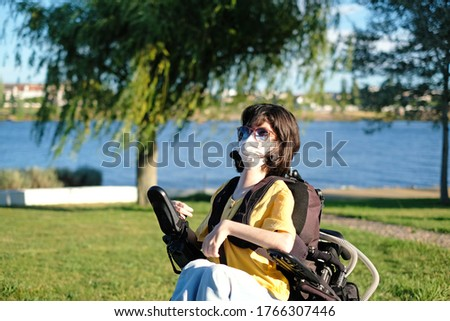 Disabled woman with muscular dystrophy in an electric wheelchair wearing a white face mask for protection during coronavirus outbreak Royalty-Free Stock Photo #1766307446
