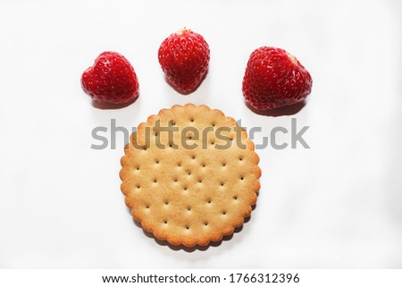 A round brown cookie with a wavy edge and small holes lies on a white surface. Above the cookies are three red strawberries of different sizes. Dessert. Close-up, top view. #1766312396