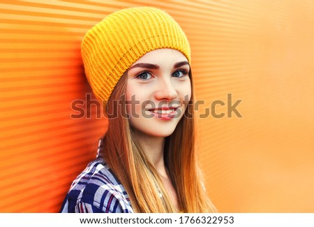 Portrait of beautiful young blonde woman wearing a yellow hat on city street over orange wall background #1766322953