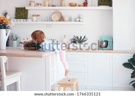 curious infant baby girl trying to reach the fruit on the table in the kitchen with the help of step stool #1766335121