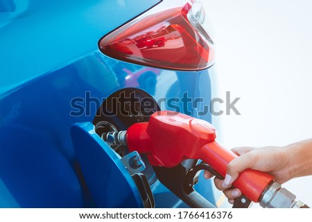Car fueling at gas station. Refuel fill up with petrol gasoline. Petrol pump filling fuel nozzle in fuel tank of car at gas station. Petrol industry and service. Petrol price and oil crisis concept. #1766416376