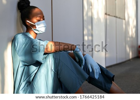 Tired exhausted female african scrub nurse wears face mask blue uniform gloves sits on hospital floor. Depressed sad black ethic doctor feels fatigue burnout stress, lack of sleep, napping at work. #1766425184