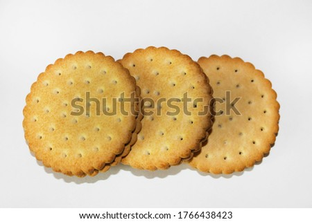 Three round cookies with wavy edges and small holes lie in a horizontal row on a white surface, one on top of the other, close-up. Dessert. #1766438423