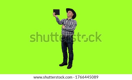 Adult man in cowboy hat taking selfie with ipad on green screen background, Chroma key