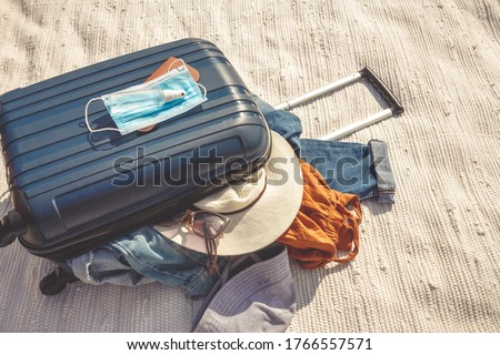 Travel.Todler sits near a suitcase with things and dreams of a vacation traveling after quarantine, lockdown, covid 19. Staycation.local travel.Tourism after the opening of borders, end of quarantine #1766557571