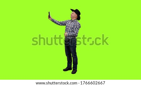 Adult man in cowboy hat taking selfie with ipad against green screen background, Chroma key