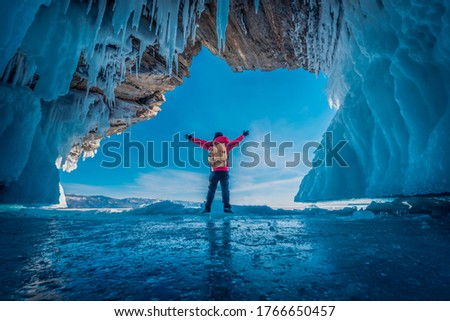 Traveler man wear red clothes and raising arm standing on frozen water in ice cave at Lake Baikal, Siberia, Russia. #1766650457