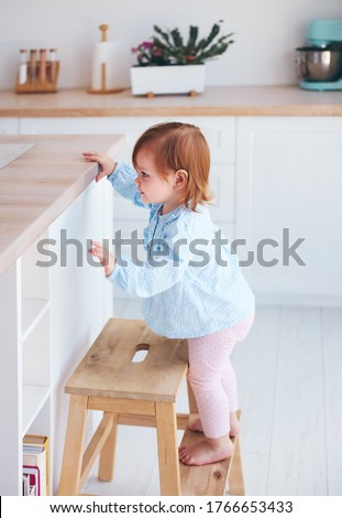 curious infant baby girl trying to reach things on the table in the kitchen with the help of step stool #1766653433