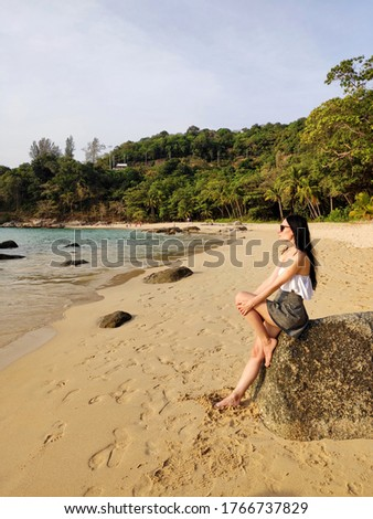 A young romantic brunette women sits on a stone, relaxes, meditates and and looks at the sunset at sea. A resting tourist. Beautiful landscape of exotic Tropical Andamand sea beach, palm trees, mounta #1766737829