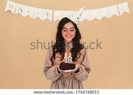 Image of happy young woman in party cone smiling while posing with birthday cake isolated over beige background