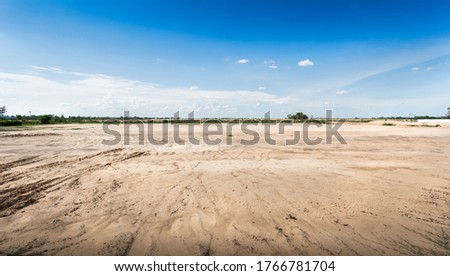 Empty dry cracked swamp reclamation soil, land plot for housing construction project with car tire print in rural area and beautiful blue sky with fresh air Land for sales landscape concept. Royalty-Free Stock Photo #1766781704