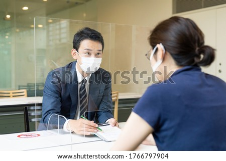 People talking across an acrylic partitions. Infection prevention. Royalty-Free Stock Photo #1766797904