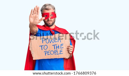 Young blond man wearing super hero custome holding power to the people cardboard banner with open hand doing stop sign with serious and confident expression, defense gesture