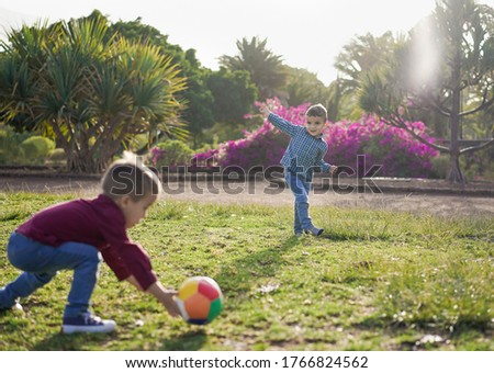 Twin brothers play together with the ball in a park - Children having a playful time together - Childhood, active and enjoying time outdoor in the nature