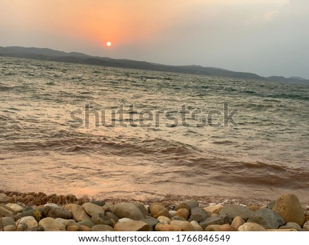 This pic show the mountains, boundary wall of Mangla lake and a boat sailing in the lake. It also contains a sunset view and the water of lake glowing.