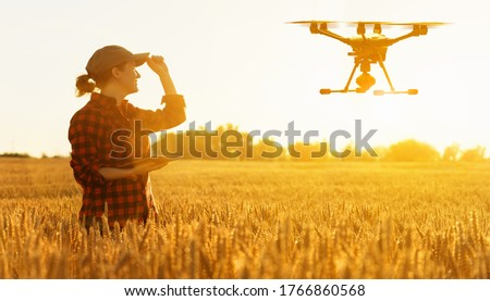 Woman farmer controls drone with a tablet. Smart farming and precision agriculture Royalty-Free Stock Photo #1766860568