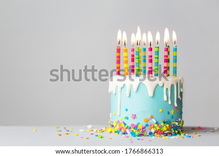 Birthday cake with white drip icing, sprinkles and colorful birthday candles Royalty-Free Stock Photo #1766866313