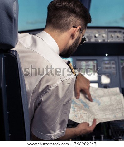 Young pilot in the aircraft in front of the dashboard. Pilot looks at the navigation map. Commercial flight.. Pre-flight preparation before the flight. Image with selestive focus.
