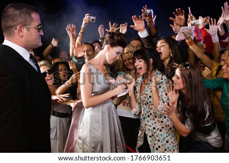 Celebrity signing autograph for screaming fans Royalty-Free Stock Photo #1766903651