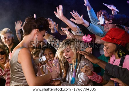 Celebrity signing autograph for screaming fans Royalty-Free Stock Photo #1766904335
