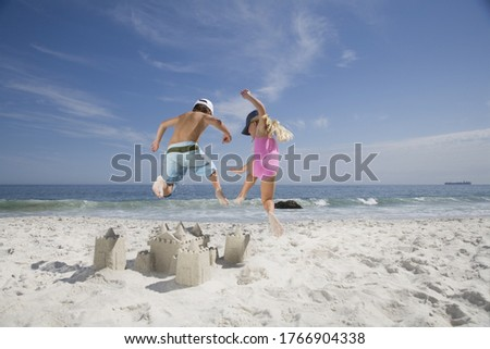 Brother and sister jumping on sandcastle on beach #1766904338