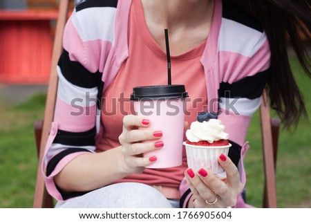 Pink disposable coffee Cup and cake in women's hands on the street. #1766905604