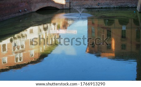 Ferrara, Italy. Moat of the Este castle, buildings reflected in the water.  #1766913290