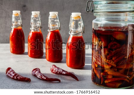 Four small bottles of chili hot sauce made from fermented dry de Cayenne chilies. Jar with fermentation process and dry chilies in front. #1766916452