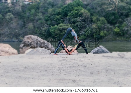 Three girls do acrobatic yoga on the banks of the Ganges River in Rishikesh, India.  Mount pose.  In nature, group classes.  Varieties of Modern Hatha Yoga #1766916761