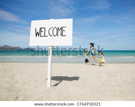 Mother and children walking behind Welcome sign at beach Royalty-Free Stock Photo #1766918321