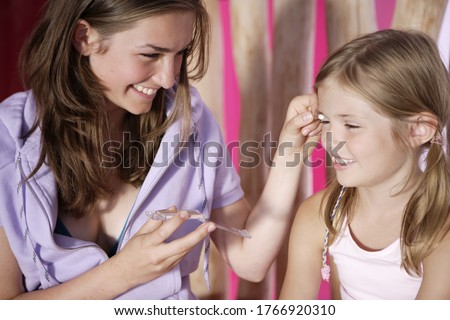 Older sister applying eye shadow for younger sister