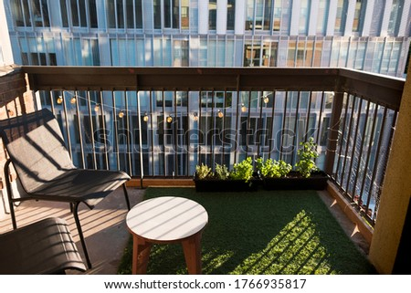 Apartment balcony in city with grass turf and potted plants. Evening light. Royalty-Free Stock Photo #1766935817