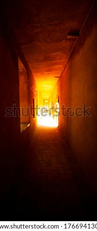 An abstract image featuring a narrow, dark corridor in an old stone building. Light penetrates towards the end providing a light at the end of a tunnel perspective and a good depth of field. #1766941304