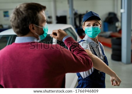 Female car mechanic and her customer greeting with elbows while wearing protective face masks in auto repair shop during coronavirus epidemic.  Royalty-Free Stock Photo #1766946809