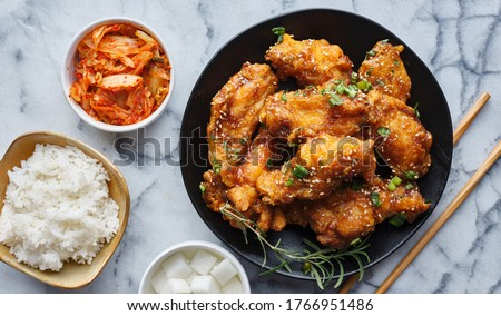 crispy fried korean chicken wings in galbi sauce with pickled radish, kimchi, and rice side dishes Royalty-Free Stock Photo #1766951486