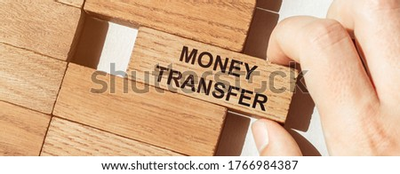 male hand pushes a piece of wood with text MONEY TRANSFER from other pieces of wood