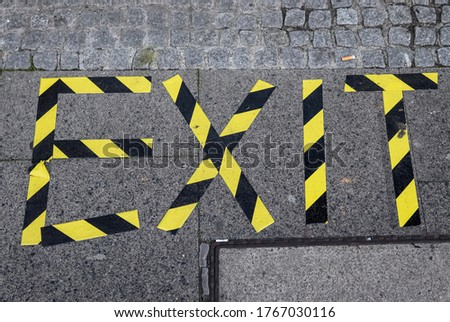 The word exit written with barrier tape onto a sidewalk #1767030116