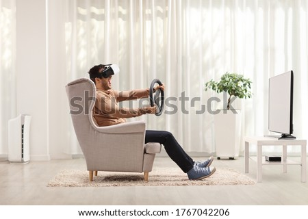Young man seated in an armchair using a virtual reality headset and holding a steering wheel at home  #1767042206