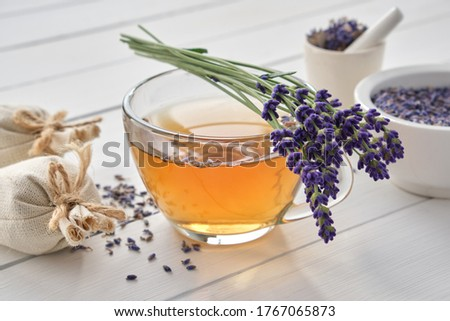 Cup of healthy lavender tea and lavender flowers. Mortars of dry lavender and sachets on background. Alternative medicine. #1767065873