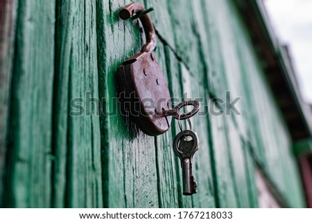 Old barn locks with keys hang on the painted green wood wall. Rusty metal device for closing doors. #1767218033