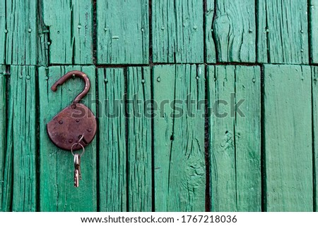 Old barn locks with keys hang on the painted green wood wall. Rusty metal device for closing doors. #1767218036