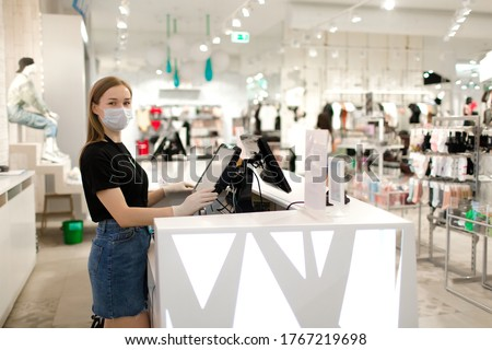Girl seller in a mask and gloves stands at the checkout in a store. Store seller during COVID-19. Safety during the virus. The seller in the clothing store. Royalty-Free Stock Photo #1767219698